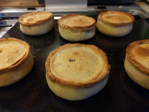 Six scotch pies sitting on a baking tray
