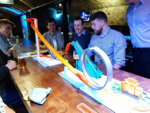 Group of people in a pub with a toy track on the table.